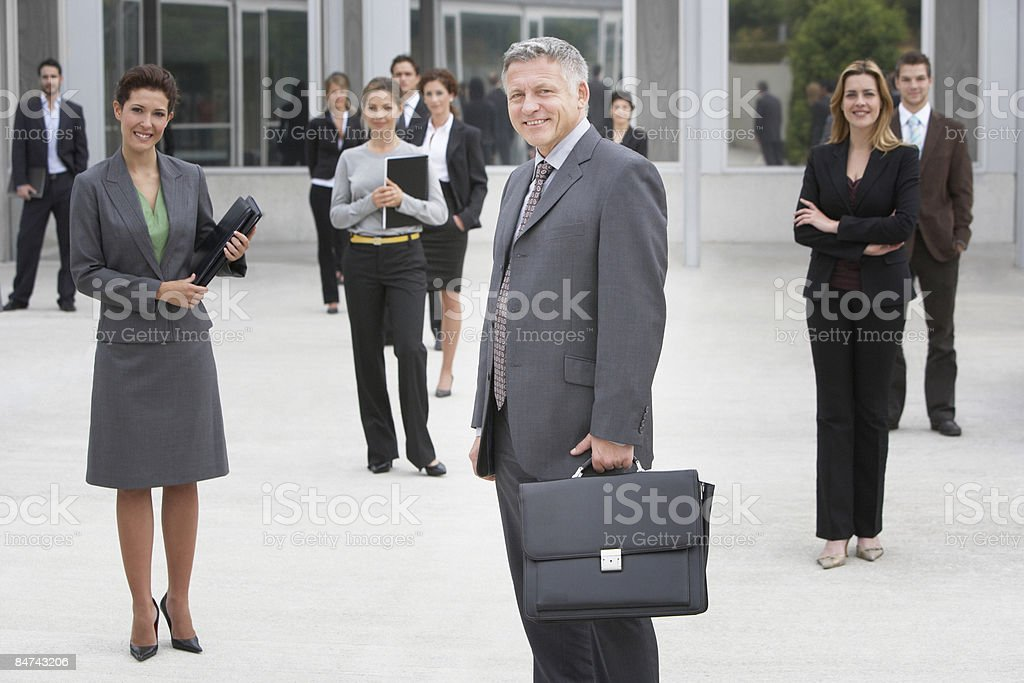 Businesspeople posing in office building courtyard royalty-free stock photo