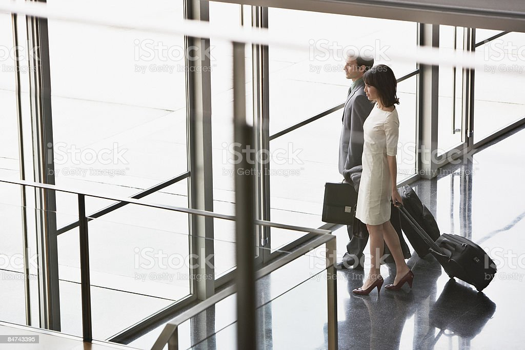 Businesspeople pulling suitcases in lobby royalty-free stock photo