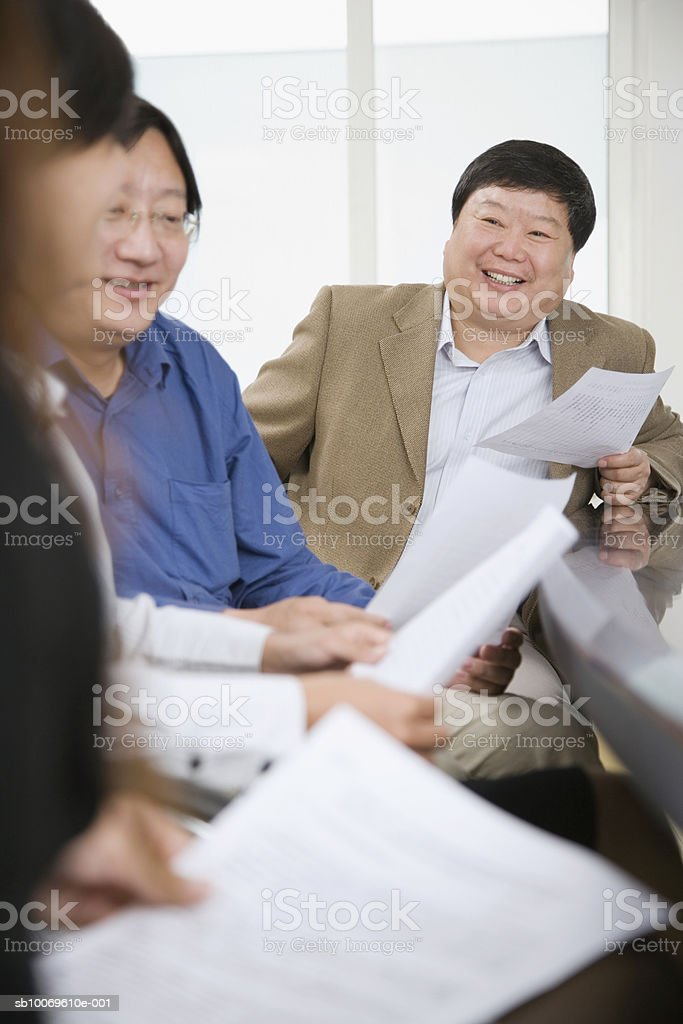 Businesspeople reading documents in conference room, smiling royalty-free stock photo