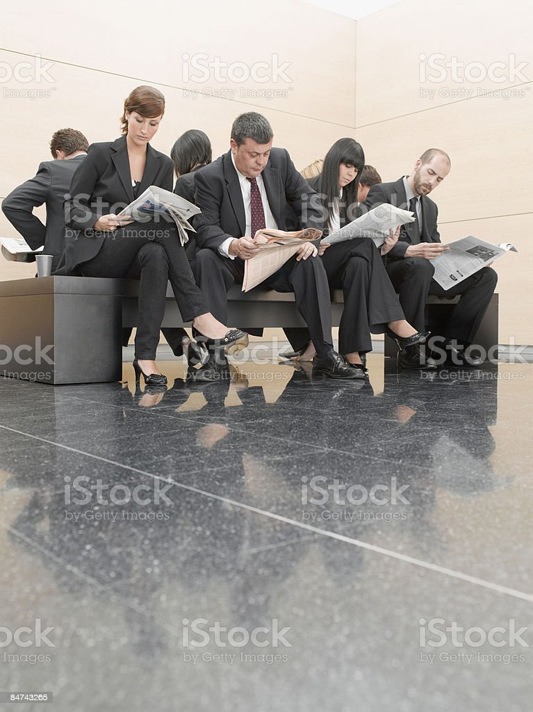 Businesspeople reading newspapers on office bench royalty-free stock photo