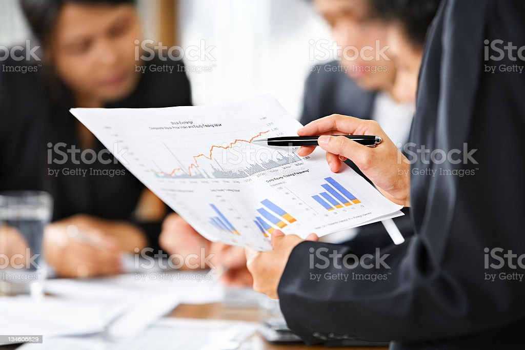 Businesspeople reviewing documents and graphs stock photo