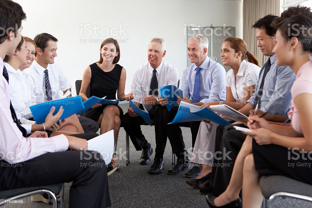 Businesspeople Seated In Circle At Company Seminar stock photo