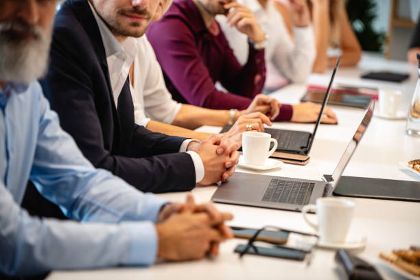 Businesspeople Seated Side by Side at Conference Table stock photo