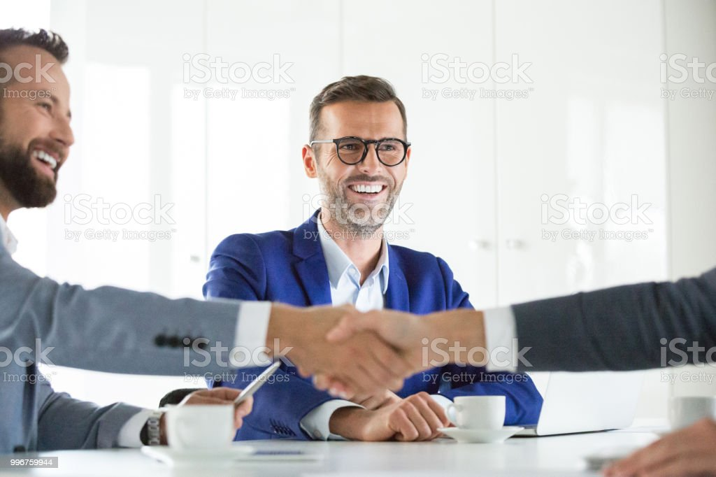 Businesspeople shaking hands after a deal Two business man shaking hands after successful deal with coworker looking and smiling. Successful business deal. Adult Stock Photo