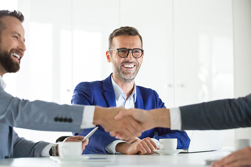 Businesspeople Shaking Hands After A Deal Stock Photo - Download Image Now