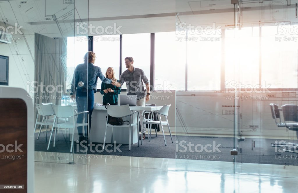 Businesspeople shaking hands after successful meeting stock photo