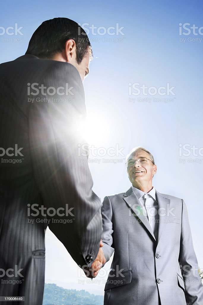 Businesspeople shaking hands against the sky. royalty-free stock photo