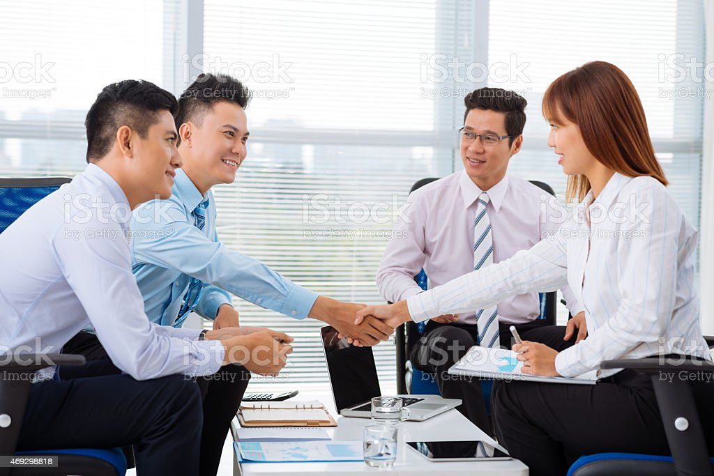 Businesspeople shaking hands and looking pleased stock photo