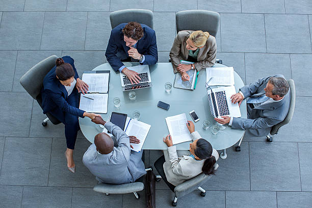 businesspeople shaking hands at conference table - business meeting, table view from above foto e immagini stock