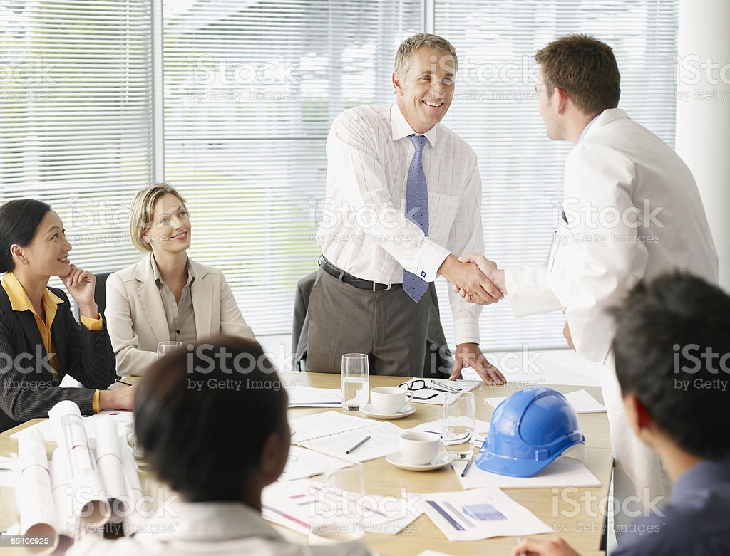 Businesspeople shaking hands in conference room royalty-free stock photo