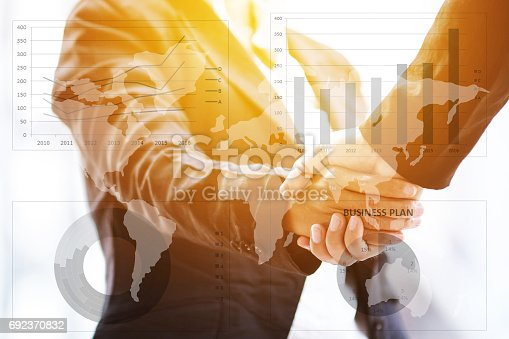 istock Businesspeople shaking hands on business graph background. 692370832