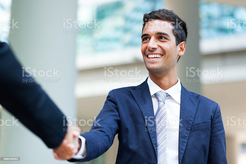 Hombres de negocios estrechándose las manos al aire libre - foto de stock