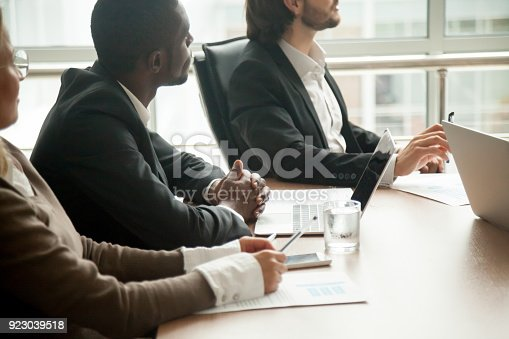 istock Businesspeople sitting at conference table focused on listening at meeting 923039518