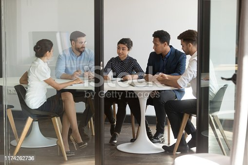 istock Businesspeople sitting at table in boardroom listens indian team leader 1174262736