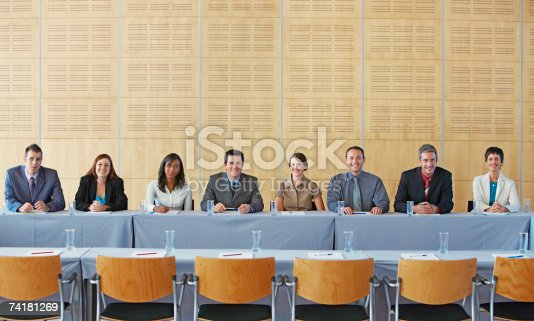 84743203 istock photo Businesspeople sitting at table smiling 74181269