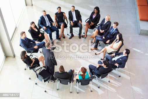 504879112istockphoto Businesspeople sitting in a circle with one of them standing 469718177