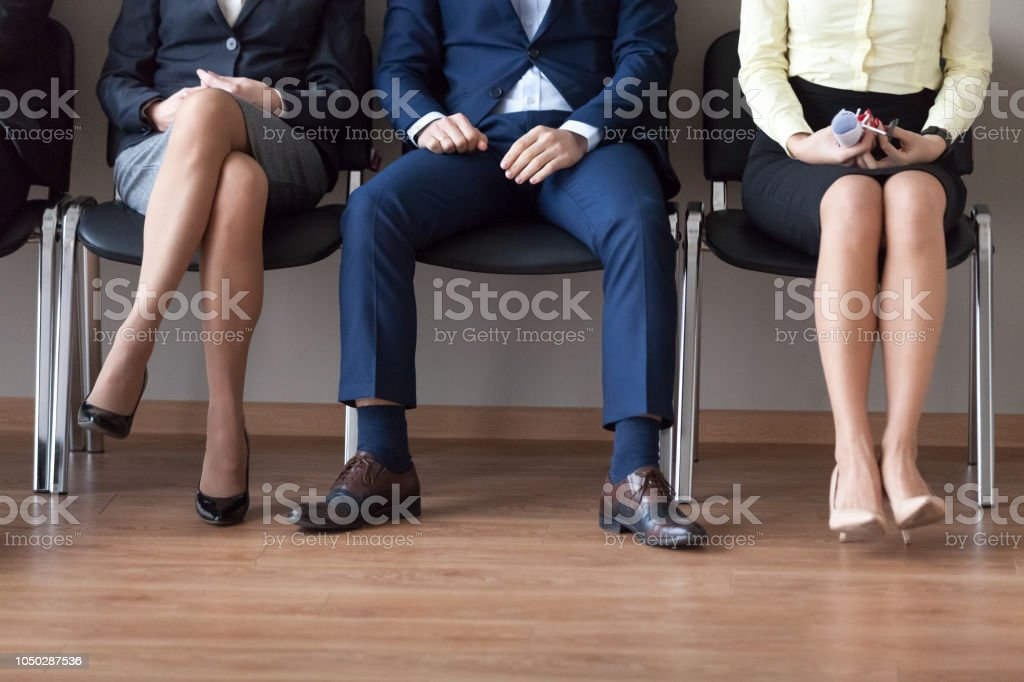 Businesspeople sitting in chairs in queue waiting job interview stock photo