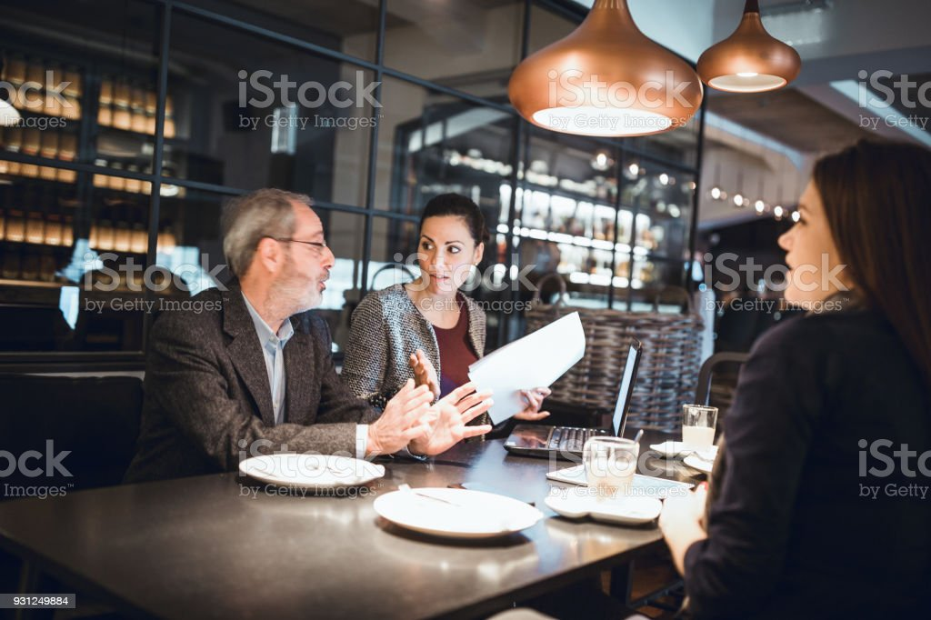 Businesspeople sitting in restaurant and having meeting stock photo