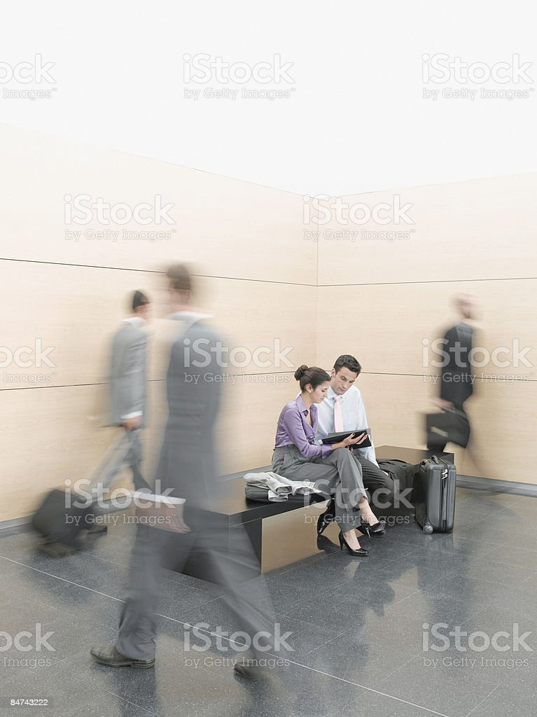 Businesspeople sitting on bench in lobby royalty-free stock photo