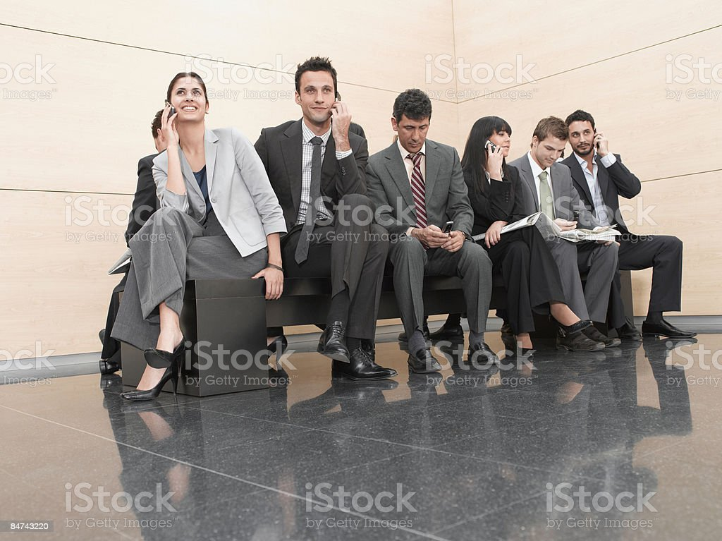 Businesspeople sitting on crowded bench royalty-free stock photo