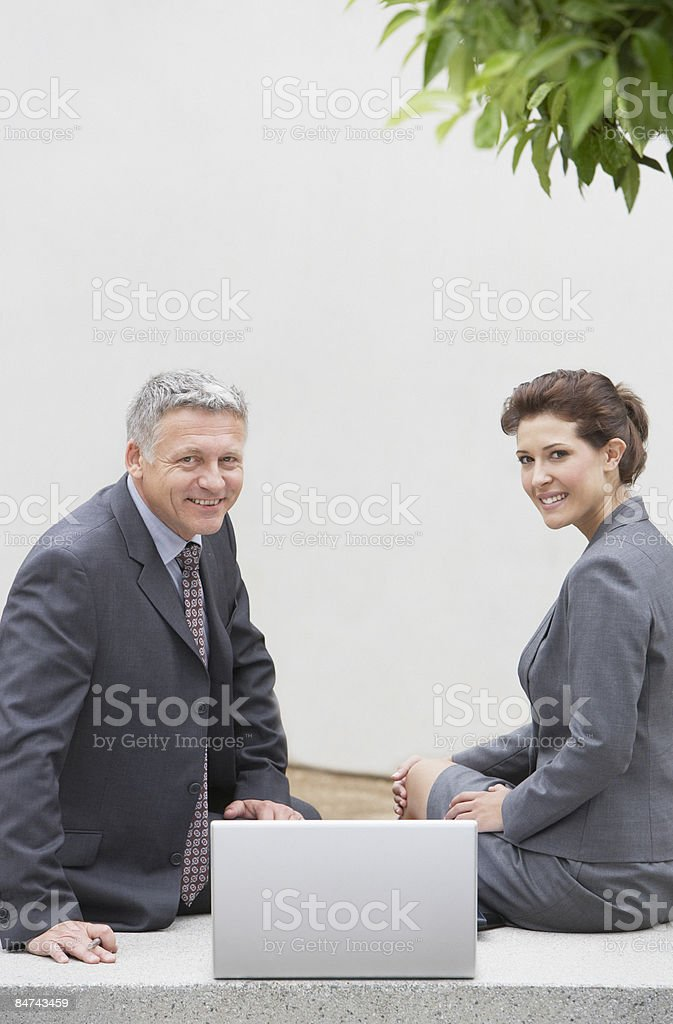 Businesspeople sitting with laptop in courtyard royalty-free stock photo