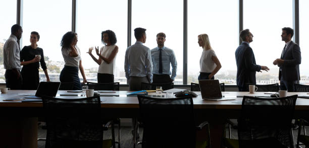 Businesspeople Stand And Chat Before Meeting In Boardroom Businesspeople Stand And Chat Before Meeting In Boardroom letterbox format stock pictures, royalty-free photos & images
