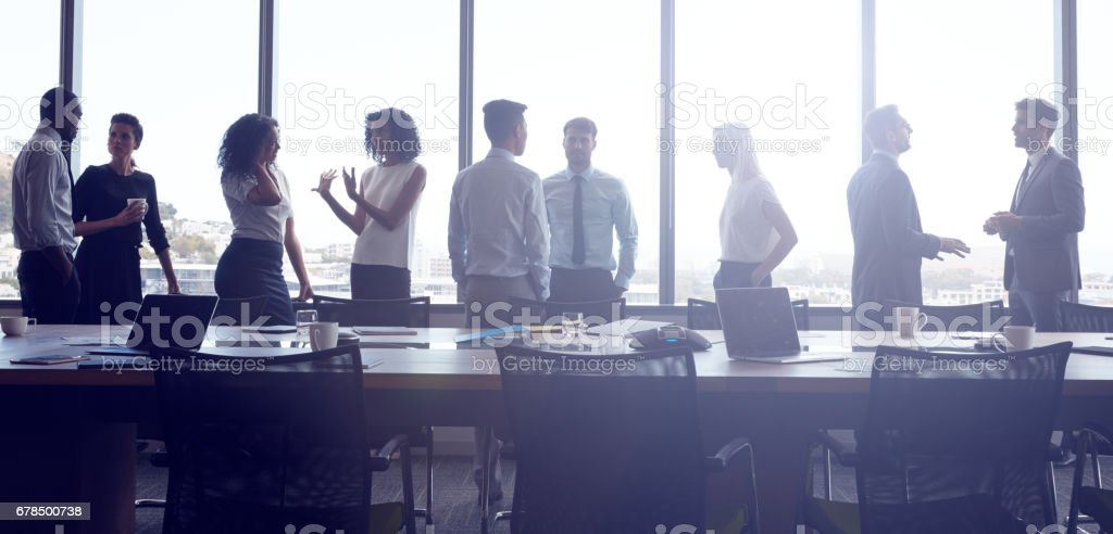 Businesspeople Stand And Chat Before Meeting In Boardroom stock photo