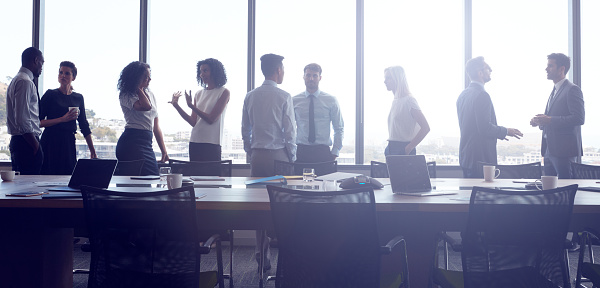 Businesspeople Stand And Chat Before Meeting In Boardroom Stock Photo - Download Image Now