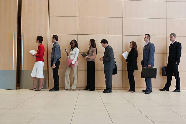 hommes d'affaires, debout dans une ligne - queue photos et images de collection