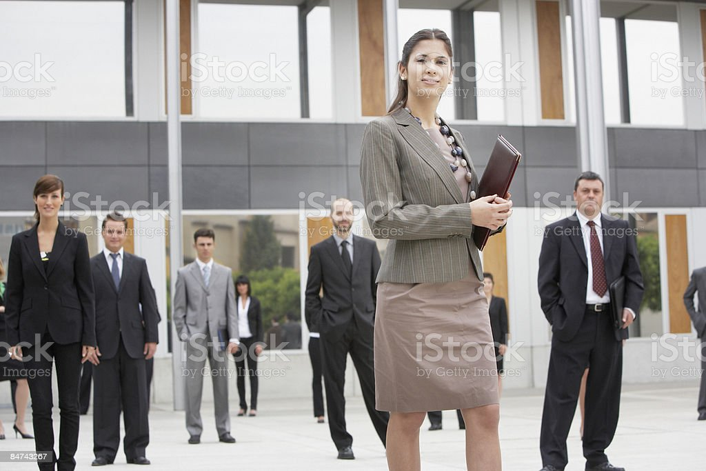 Businesspeople standing in office building courtyard royalty-free stock photo
