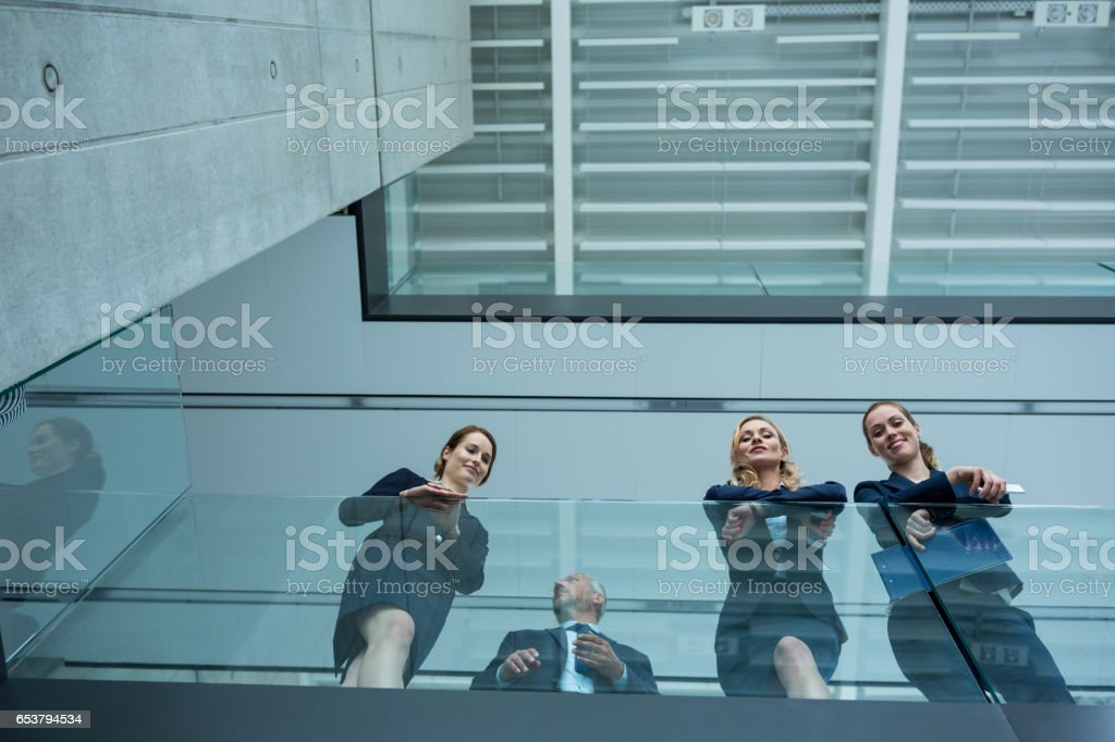 Businesspeople standing in office stock photo