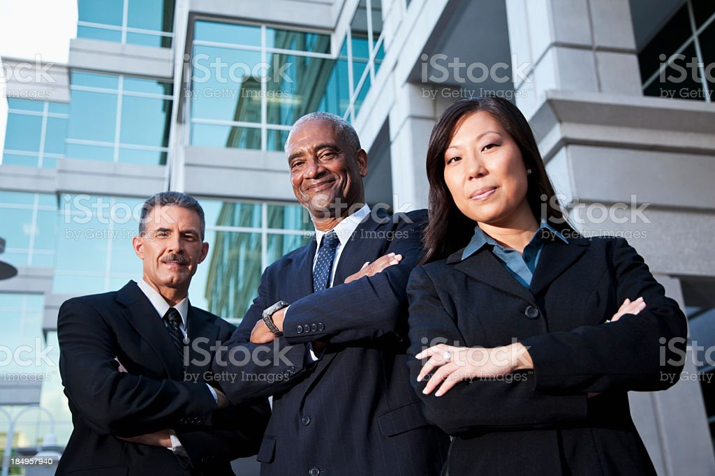 Businesspeople standing outside office building stock photo