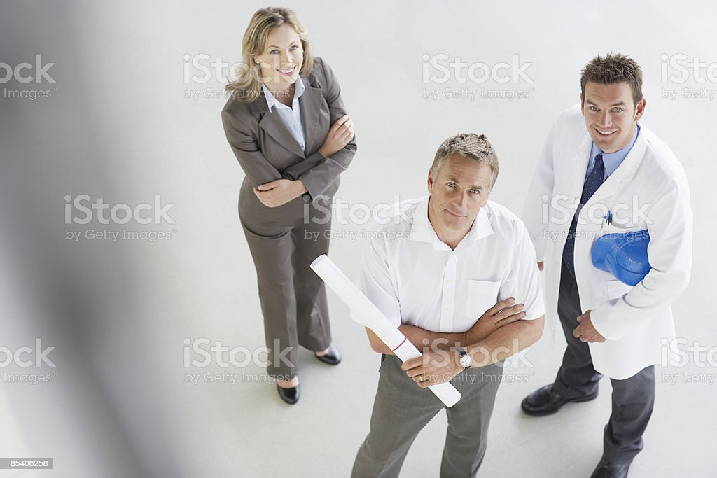 Businesspeople standing with blueprints 免版稅 stock photo