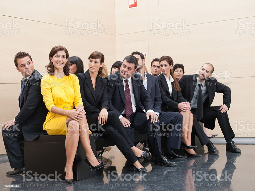Businesspeople staring at unique co-worker stock photo