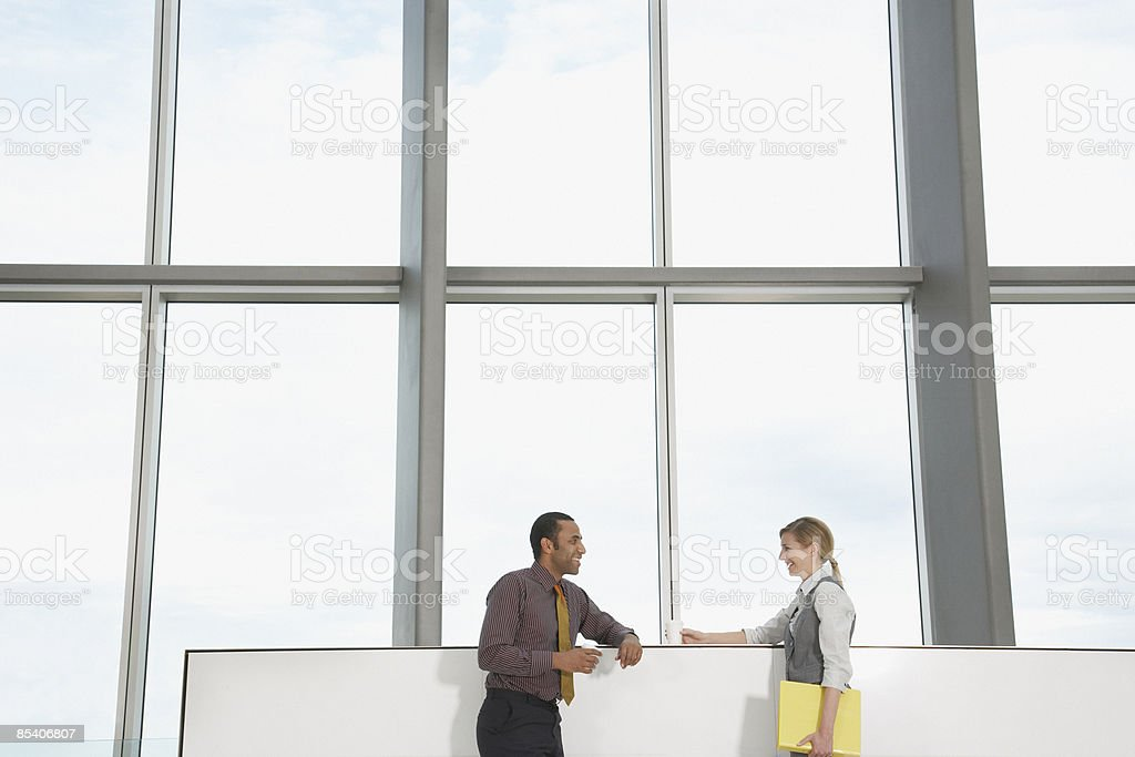 Businesspeople talking near window royalty-free stock photo
