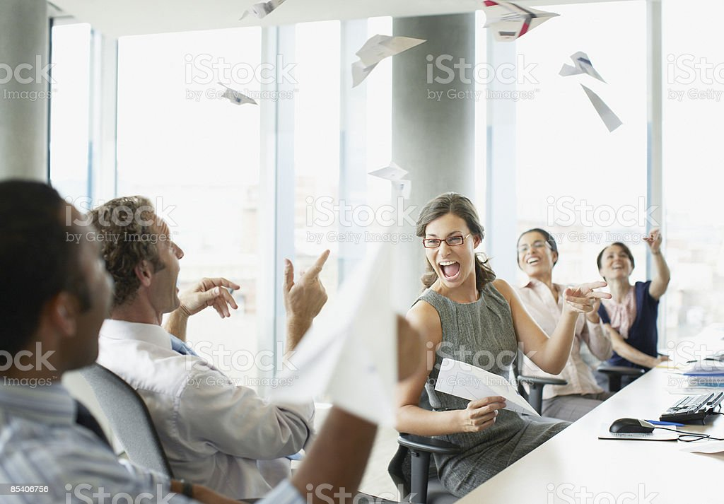 Businesspeople throwing paper airplanes in office stock photo