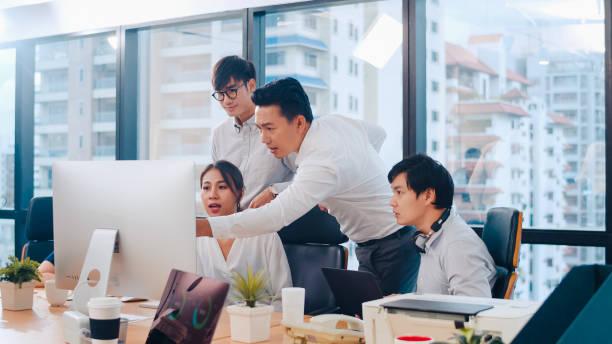 Geschäftsleute, die Computerpräsentation und Kommunikation nutzen, treffen Brainstorming-Ideen über Projektkollegen, die im modernen Büro eine Erfolgsstrategie planen. – Foto