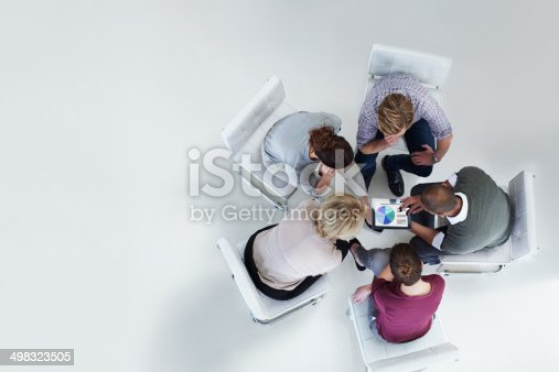 High angle view of businesspeople using digital tablet together in office