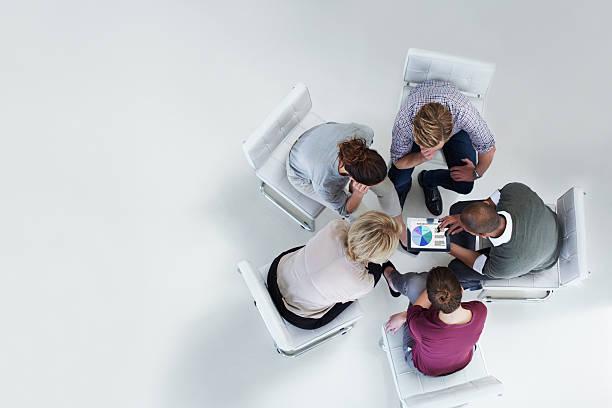 businesspeople using digital tablet together - draufsicht stock-fotos und bilder
