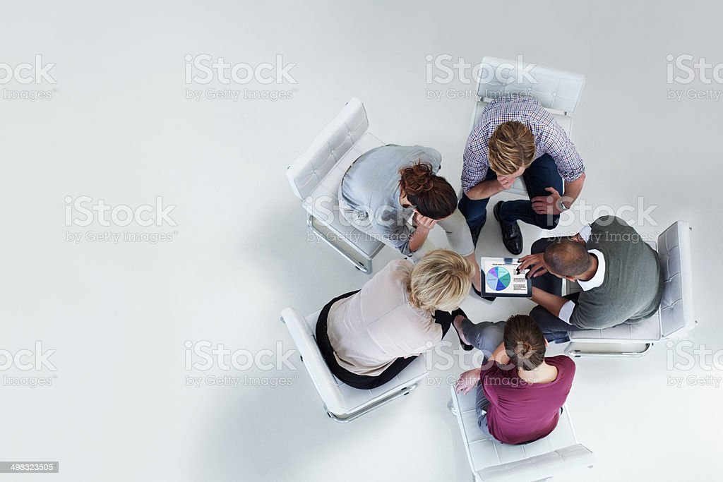 Businesspeople using digital tablet together stock photo