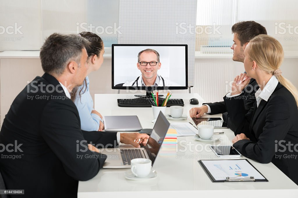 Businesspeople Videoconferencing With Doctors stock photo