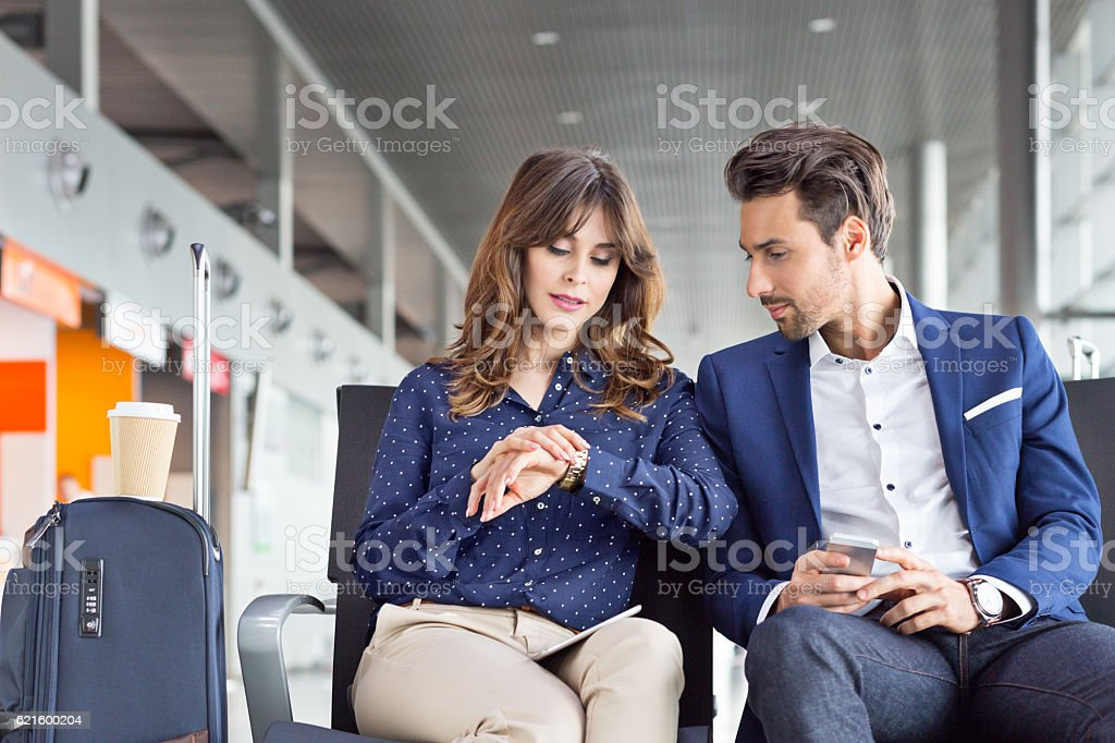 Businesspeople waiting for flight at airport lounge stock photo