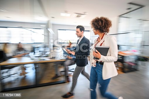 1163429625istockphoto Businesspeople Walking and Talking on the Way to a Meeting 1162941365