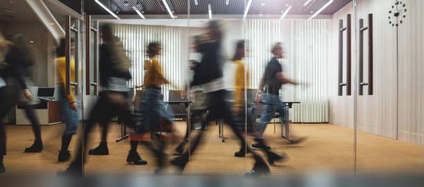 Geschäftsleute, die in einem modernen Büro spazieren gehen. Gruppe von Mitarbeitern im Coworking Center. Bewegungsunschärfe. Konzeptarbeitsprozess. Breites Bild – Foto
