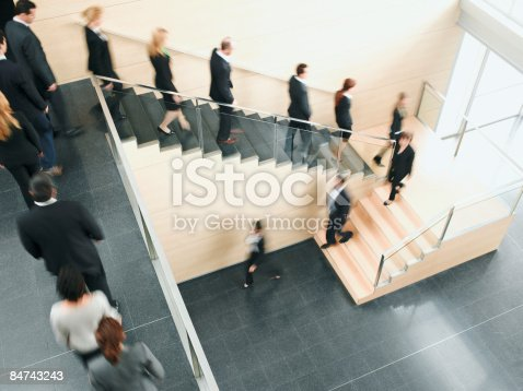 84743203 istock photo Businesspeople walking down office staircase 84743243