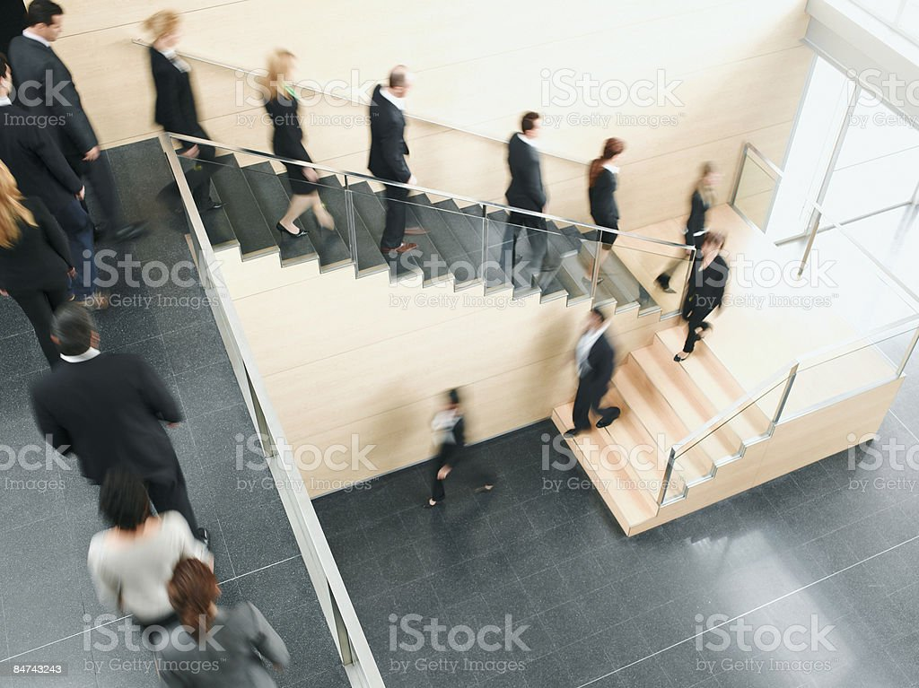 Businesspeople walking down office staircase stock photo
