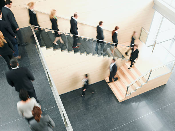 Businesspeople walking down office staircase  downsizing unemployment stock pictures, royalty-free photos & images