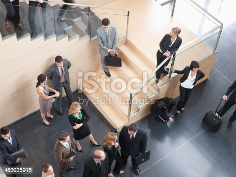 istock Businesspeople walking in busy office building 483635915