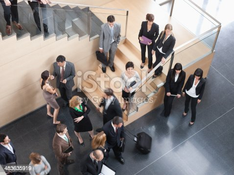 483635979 istock photo Businesspeople walking in busy office building 483635919