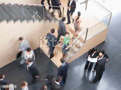 483635979 istock photo Businesspeople walking in busy office building 483635923